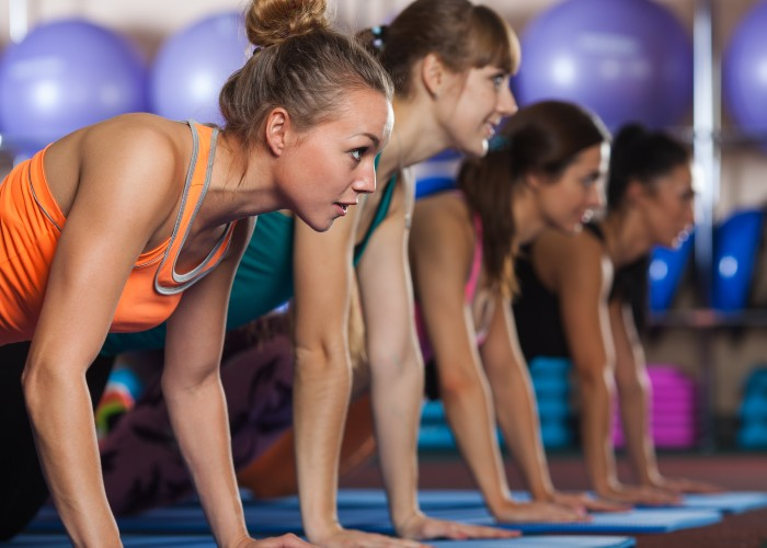 group of women doing plank in semi-private training class